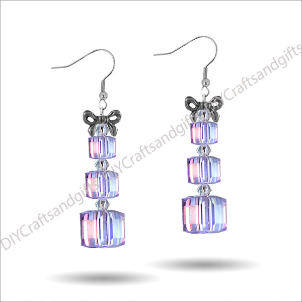 Beautiful Handmade Swarovski Crystal Earrings. The perfect gift for Christmas!Choose between Silver Plated, Gold Plated, Sterling Silver and 9ct Yellow Gold findings.These presents have Bow on the top (gold or silver - matching the findings), a Crystal bicone, small Violet (purple) present, Crystal bicone, medium Violet (purple) present, Crystal bicone and a large Violet (purple) present.Approx. 35mm long x 14mm wide (at top of bow)