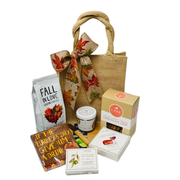 """Whether it's Thanksgiving with your family or Friendsgiving with your closest pals, offering the hostess with the mostess a gift to show your gratitude and appreciation is always a good idea.  This Fall themed hostess gift contains 1lb """"Fall In Love"""" Ground Coffee, Salted Caramel Almond Chocolate Chip Cookies, Jocelyn & co; mixed nuts, Cabernet Sauvignon & Cheddar Cheese Spread, Olive Oil & Sea Salt Crackers, 5 x 8 Bamboo Cutting Board with a spreader and Cocktail Napkins in a Jute Tote finished with a matching bow."""