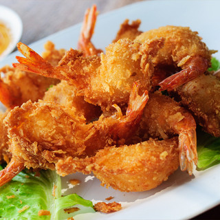 Crispy coconut tail-on coconut shrimp styled on a rectangular serving plate.