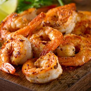 Freshly grilled seasoned shrimp on a dark-wood cutting board.
