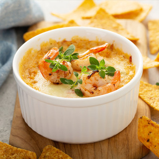A pure white ramekin filled with a scrumptious shrimp dip topped with three tail-on shrimp .