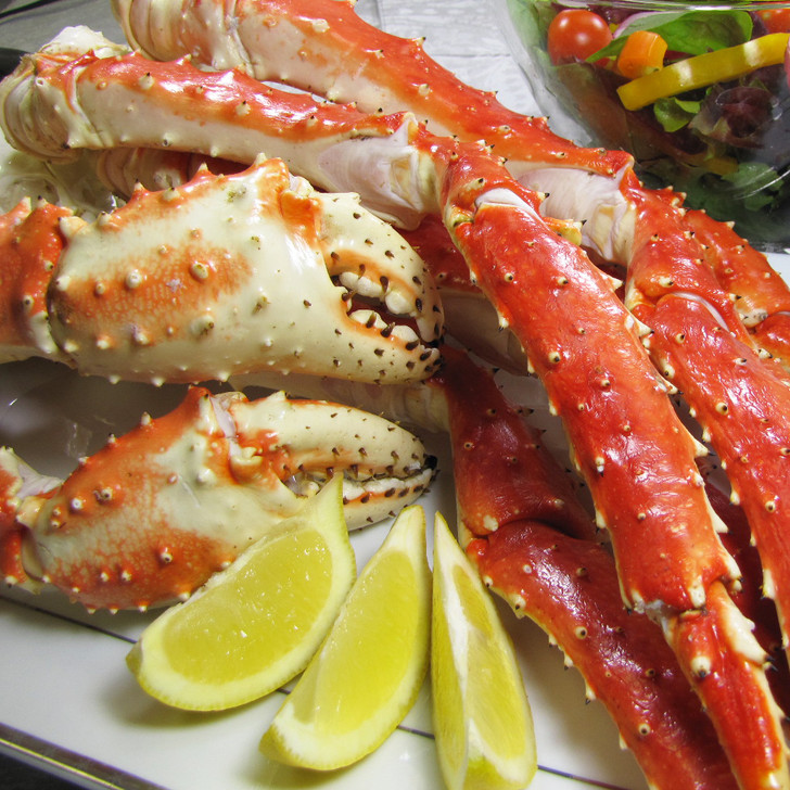 Alaska Red King Crab Legs on platter with sliced lemons.