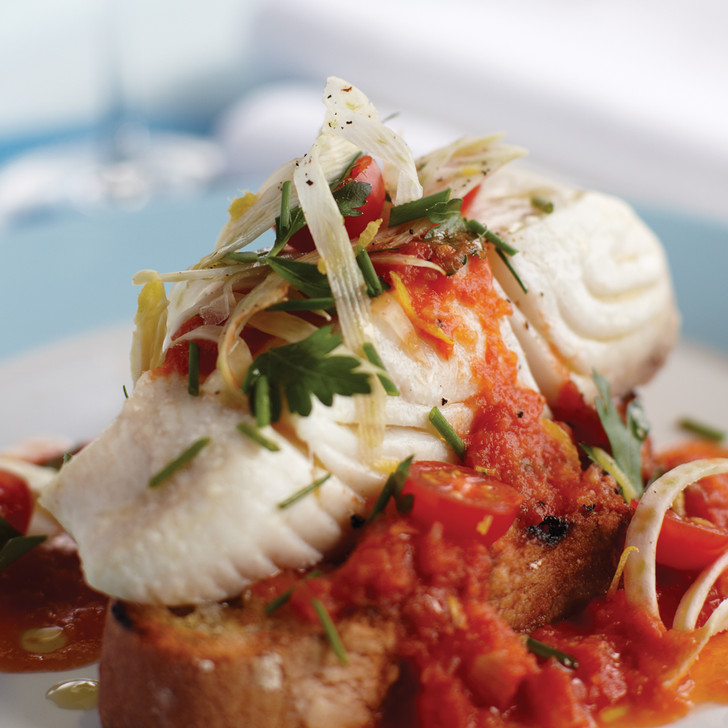 A delicious halibut fillet entrée with tomatoes.