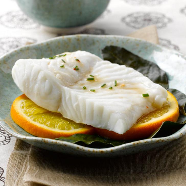 Cooked halibut fillet portion on sliced orange slices.
