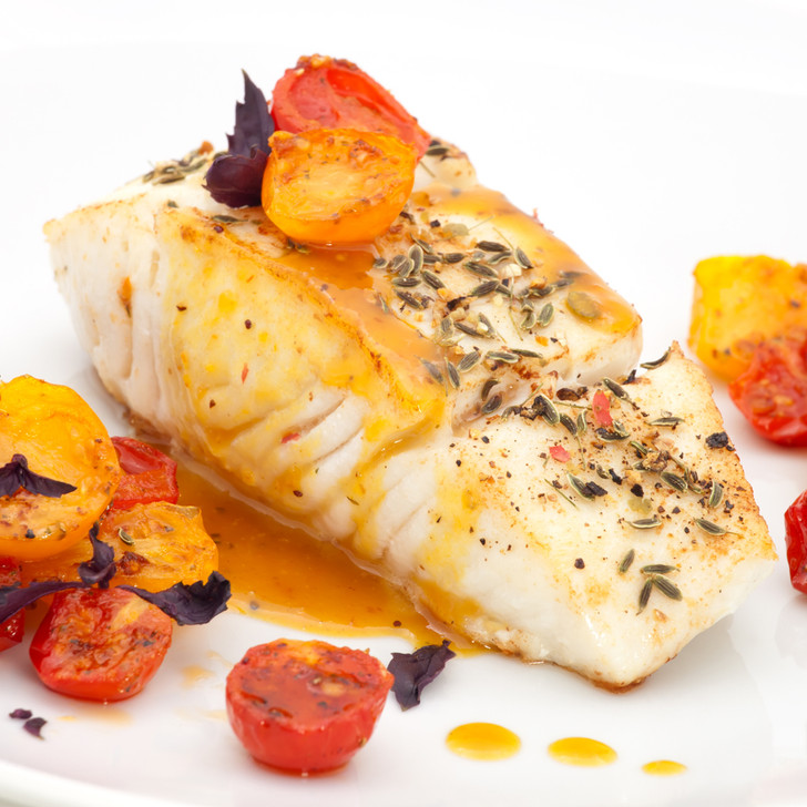 A delicious halibut fillet entrée with sliced tomatoes.