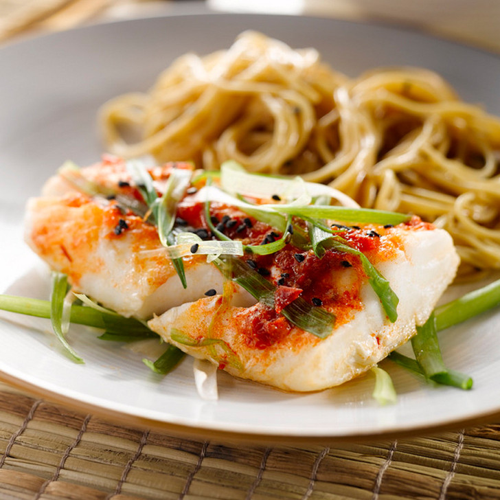 Cooked Alaska halibut tail portion on a plate with noodles.