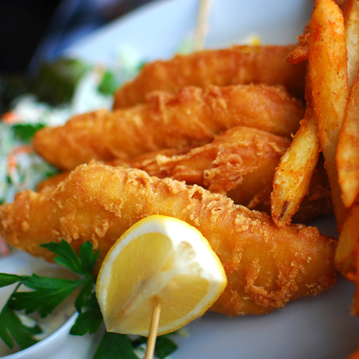 Pubhouse battered halibut fillet with french fries & lemon wedge.