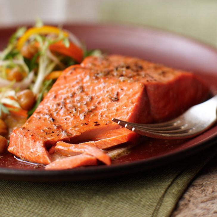 An Alaska sockeye salmon fillet partially broken apart with fork.