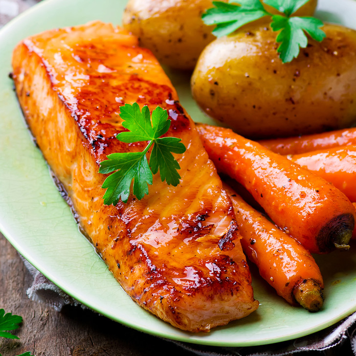 A delicious-looking dish of Copper River King salmon, garden-picked carrots, & small baked potatoes.