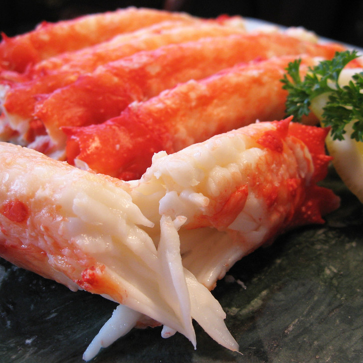 Large chunks of Alaska red king crab merus meat on marble cutting board.