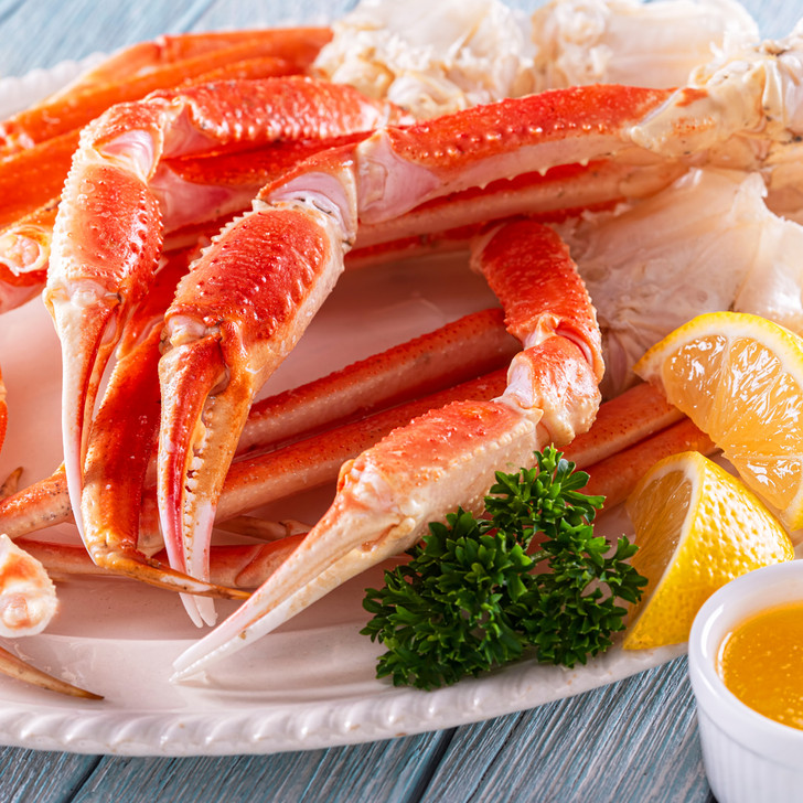 Big, giant Alaska snow crab legs & claws with lemon wedges & melted butter.