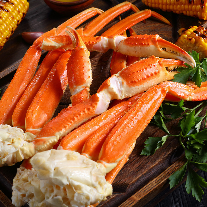 Two clusters of Alaska snow crab on cutting board with corn on the cob.