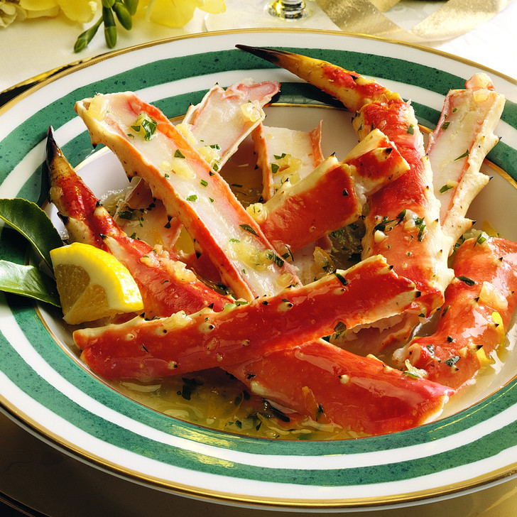Split king crab legs in a gold-rimmed bowl with butter sauce poured over top.