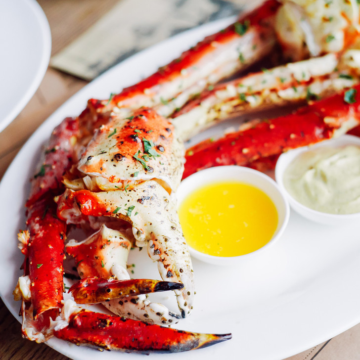 Giant king crab legs on a large white oval plate with melted butter.