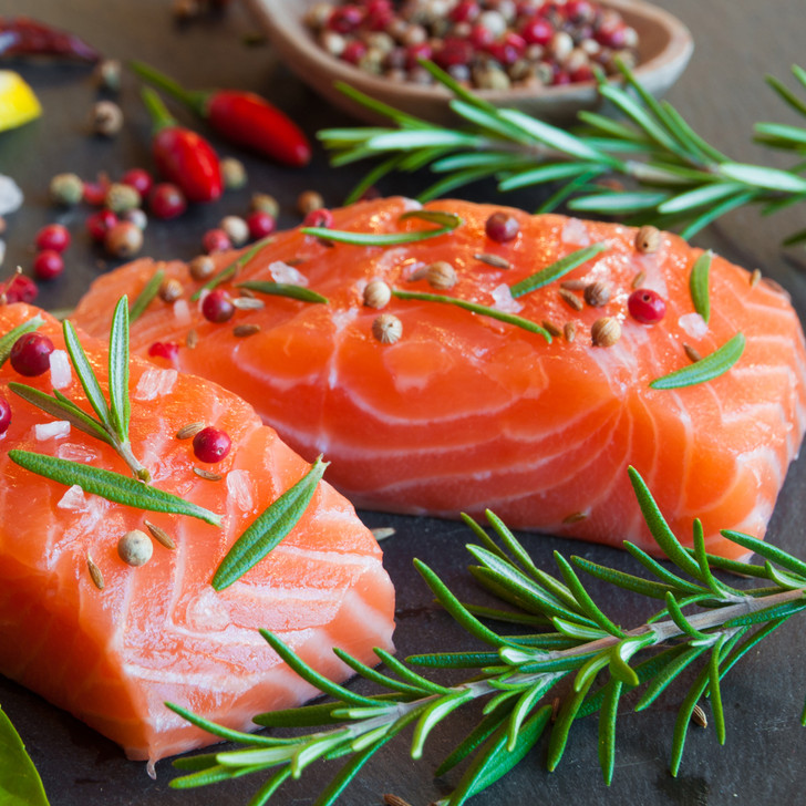 Fresh Copper River sockeye salmon fillet portions with peppercorns & herbs.