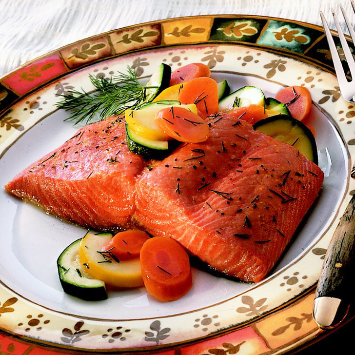 Fresh Yukon king salmon fillet portion on a plate with carrots & zucchini slices.