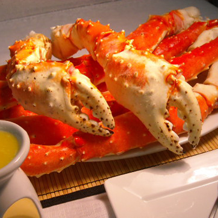 Two huge king crab claws laying over giant king crab legs.