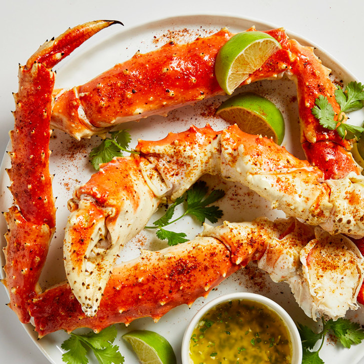 Giant king crab legs and claw displayed on a plate with limes & parsley, sprinkled with paprika.