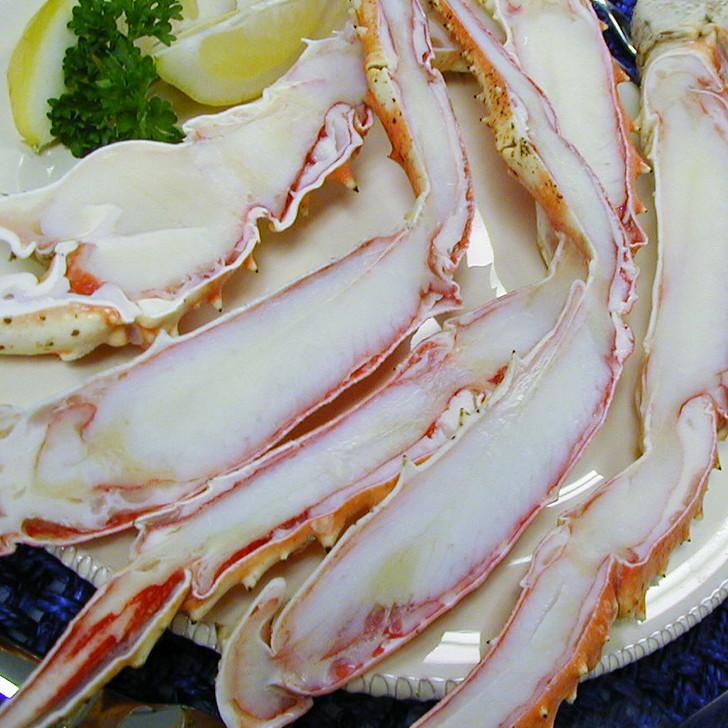 Split king crab legs on a plate with sliced lemons.