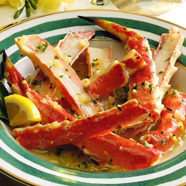 Split king crab legs served in a green-rimmed bowl with a buttery sauce.