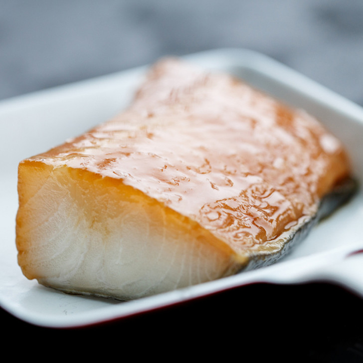 A rich and buttery broiled Alaska black cod fillet in a serving dish.