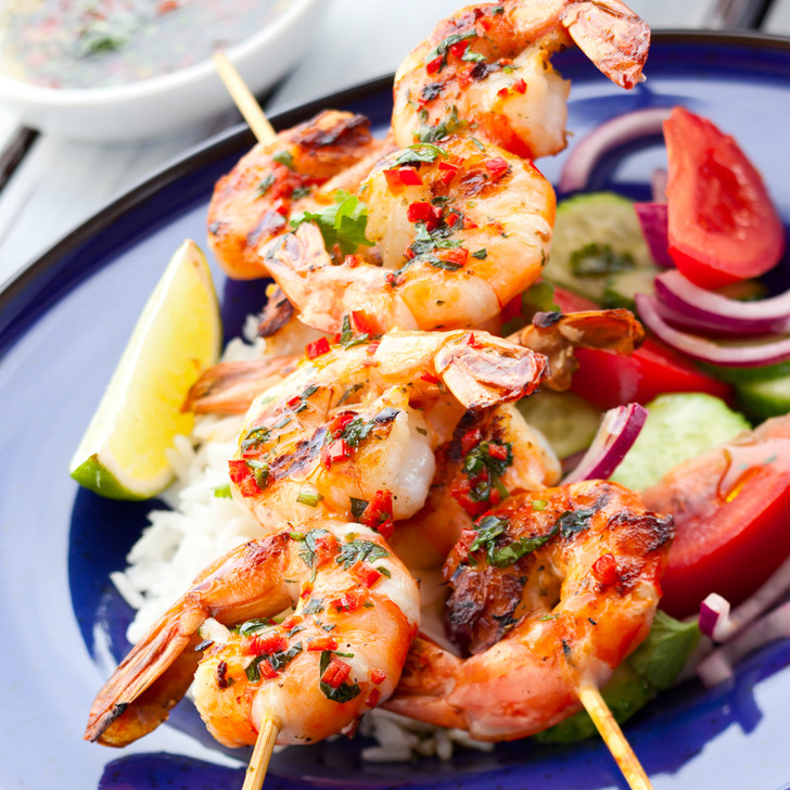 Grilled Spot shrimp skewered laying across a fresh vegetable salad with lime garnish.