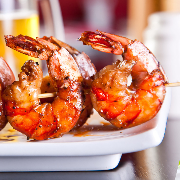 Delicious grilled jumbo shrimp on a wooden skewer.