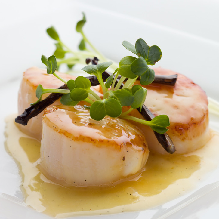 Three large caramelized scallops topped with a fancy garnish.
