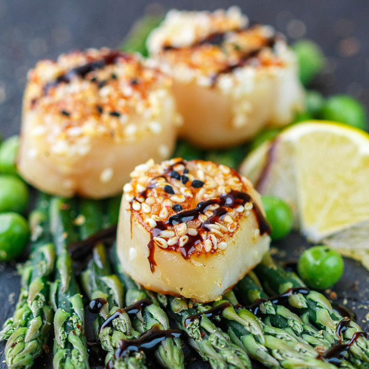 Petite Alaska scallops sprinkled with sesame seeds on top of asparagus spears.
