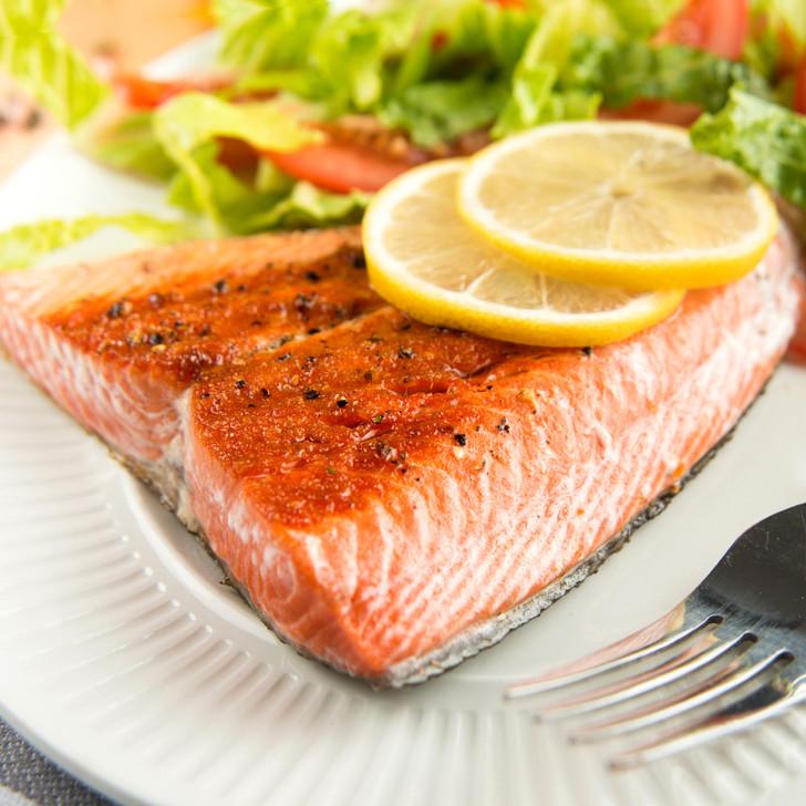 Just roasted, Alaska sockeye salmon tail portion with lemon slices and salad.