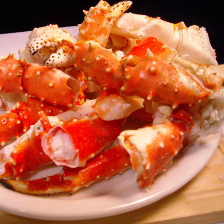 Broken king crab pieces on a white plate.