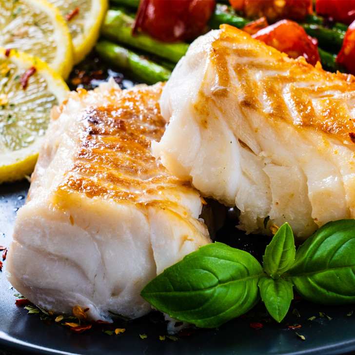 Flaky Alaska cod portions with roasted asparagus & tomatoes.