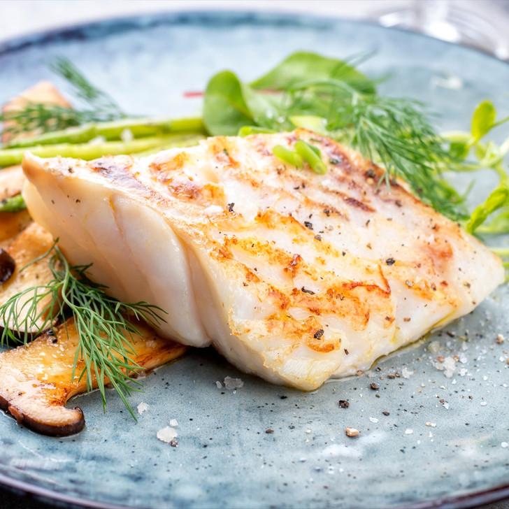 Broiled Alaska cod fillet with sliced mushrooms.