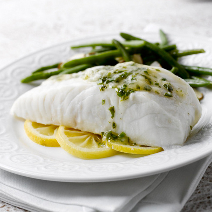 Cooked halibut fillet portion on bed of sliced lemons with green beans.
