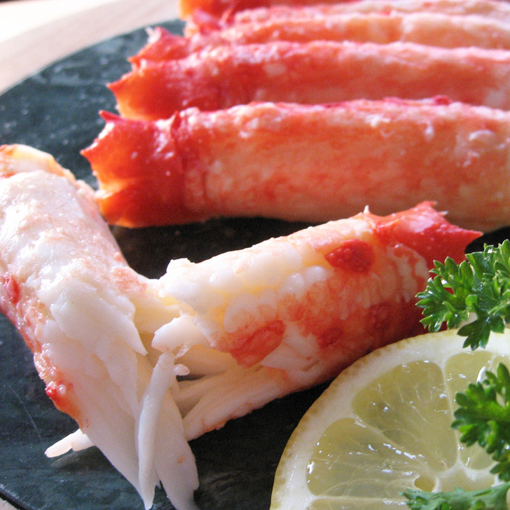 Upclose view of Alaska red king crab merus meat section torn apart.