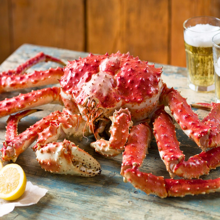 Large whole-cooked red king crab on a cutting board with lemon halves.