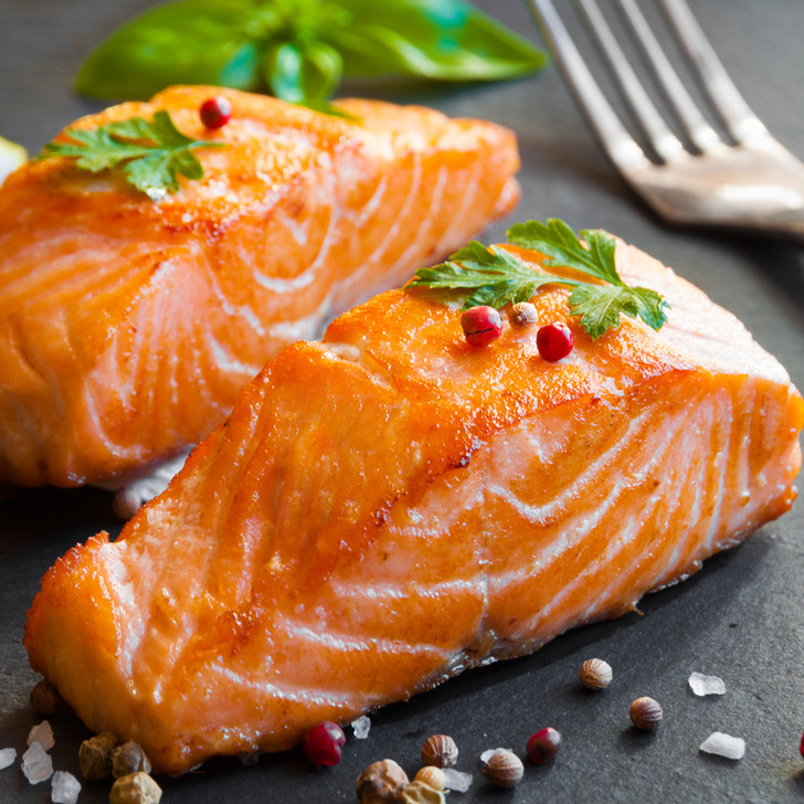 Two petite Copper River king salmon fillets with peppercorns.