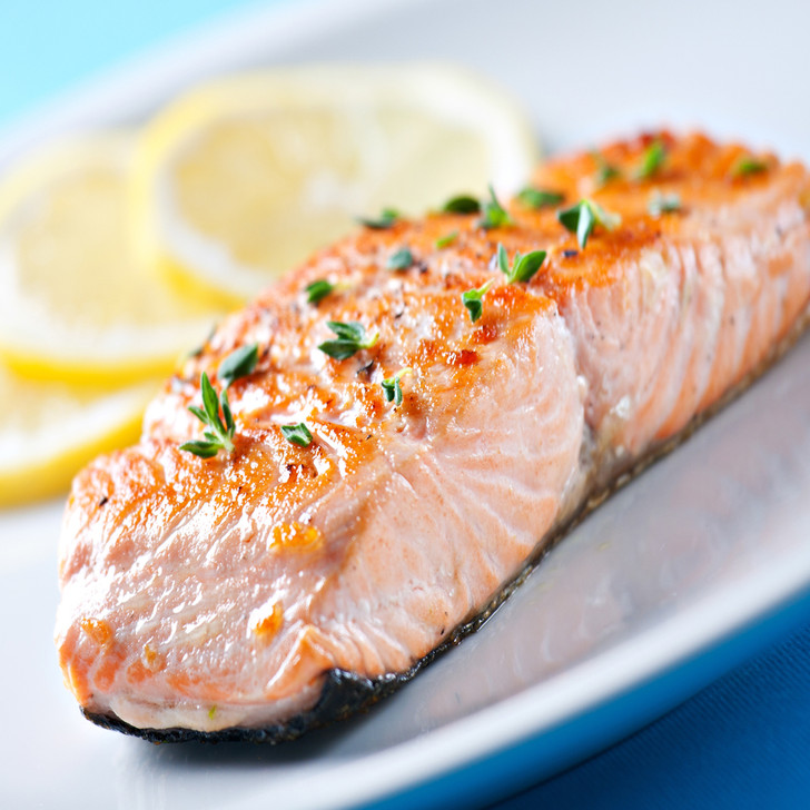 A delicious Alaska coho salmon fillet portion with lemon slices.
