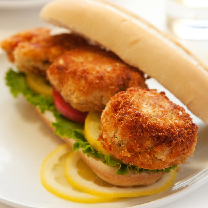 Crispy crab cake sandwich with lettuce and tomato.