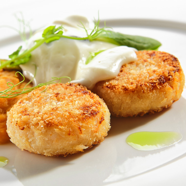 Crispy golden crab cakes with gourmet sauces.