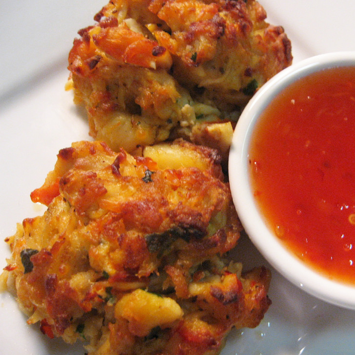 Two jumbo lump king crab cakes with dipping sauce.