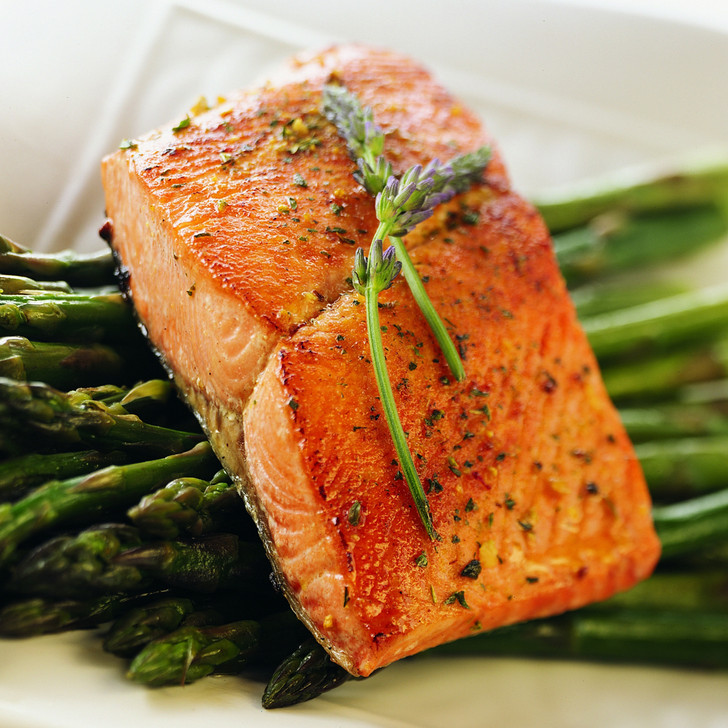 An Alaska king salmon fillet portion on top of a bed of asparagus spears.