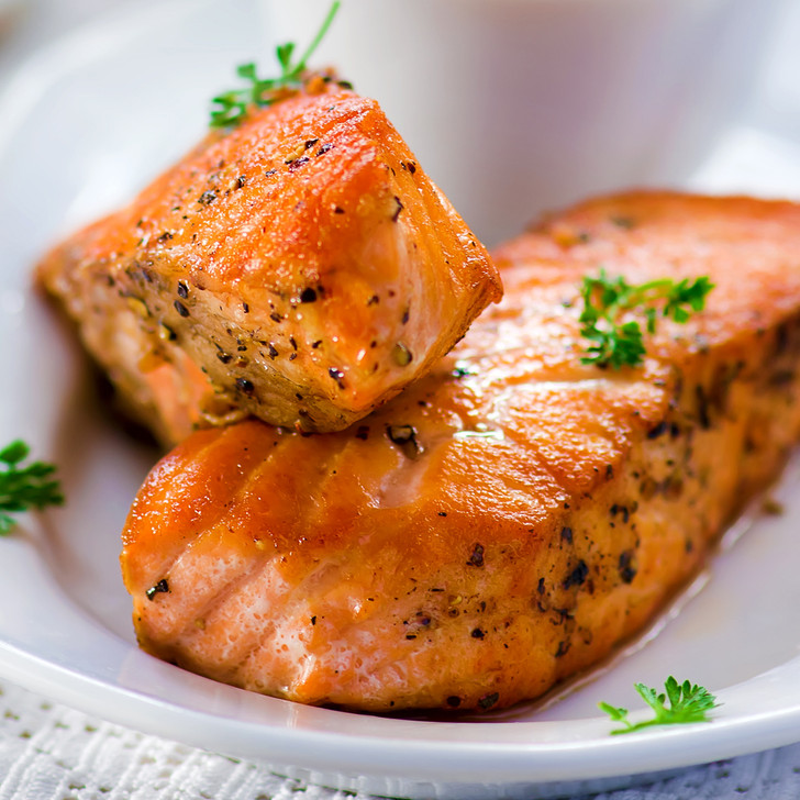 Two Alaska sockeye salmon fillet portions in a white oval dish.