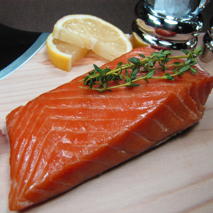 Smoked Alaska king salmon portion on cutting board with lemon slices.