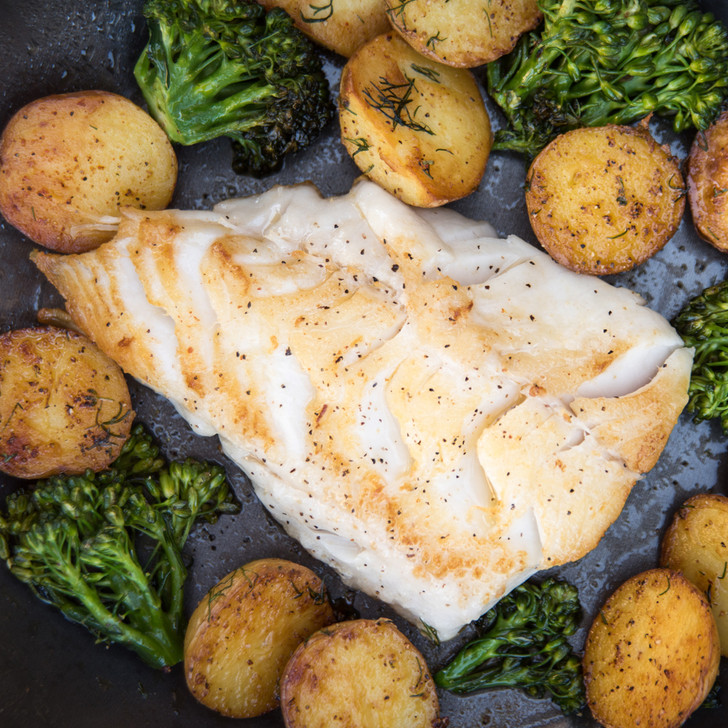 Black cod tail portion with potatoes and broccoli.