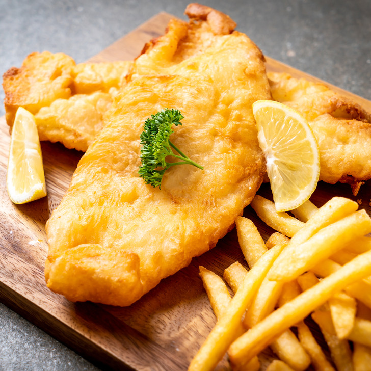 Battered cod with french fries and lemon wedges.