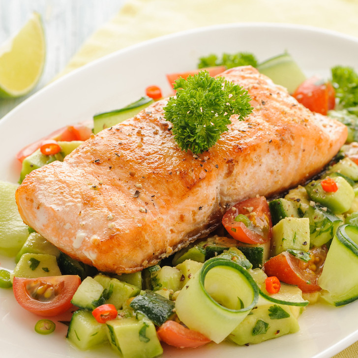 A broiled king salmon fillet on a bed of fresh diced vegetables.