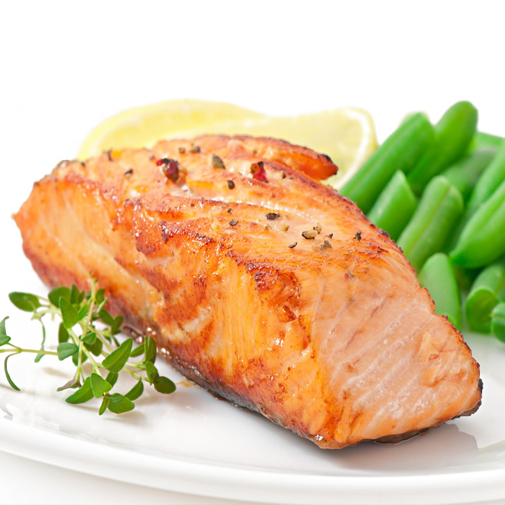 A broiled king salmon fillet on a white plate with fresh green beans & lemon wedges.