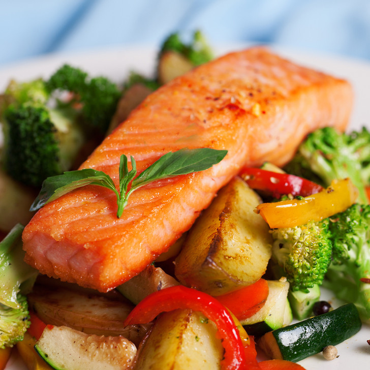 A broiled Patagonia king salmon fillet on a bed of fresh vegetables.
