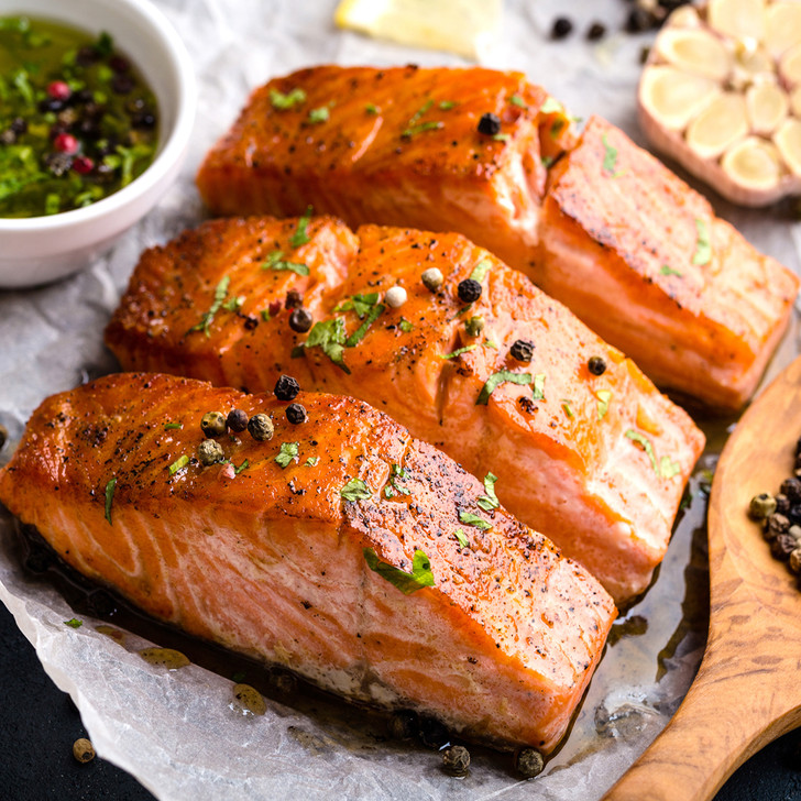 Three delicious-looking thick broiled  fillet of king salmon in a row.